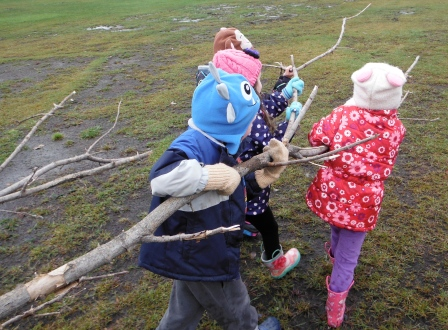 children carrying a branch