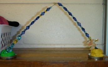 triangular sculpture with two bases and patterning of the beads between the bases