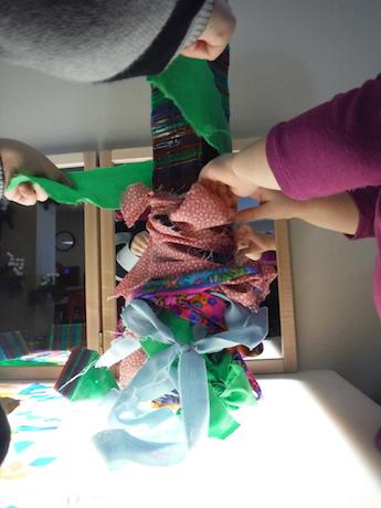 hands tyeing scraps of fabric around a plastic block tower