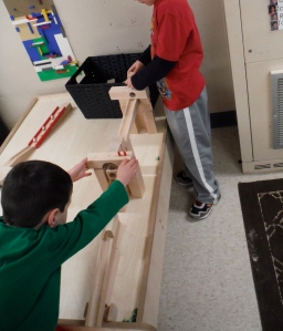boys playing with wooden marble run