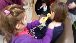 one girl using a toy otoscope to look in another girl's ear