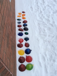 two rows of coloured balloons, filled with water, sitting in the snow