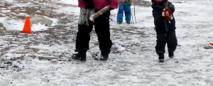 ECE and child carrying stick towards the school