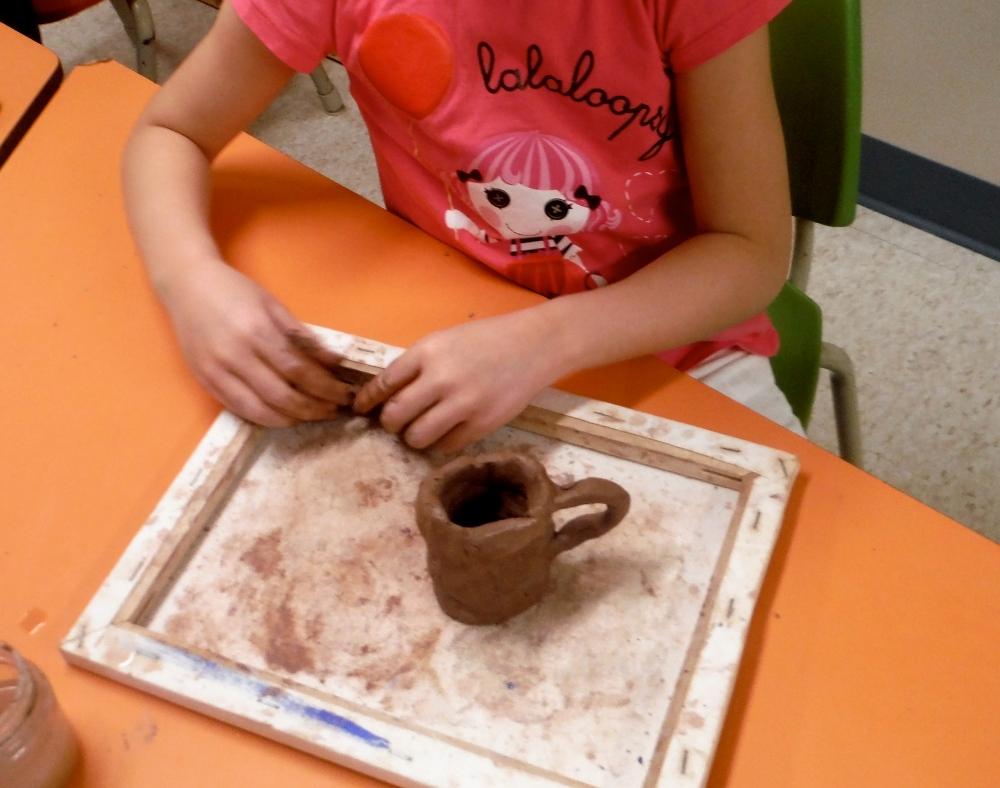 girl handbuilding a mug with clay