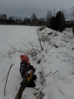 kneeling girl holding a branch next to a pile of snow