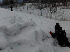 boy kneeling on snow pile, girl walking away from camera