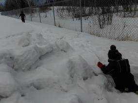 boy kneeling on snow pile, girl walking away from camera
