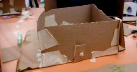 cardboard building, no roof, with door cut into the wall, masking tape doorknob