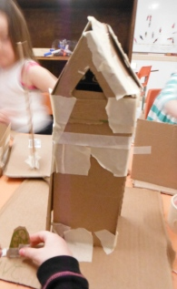 tall cardboard building with sloped roof and triangular dormer window