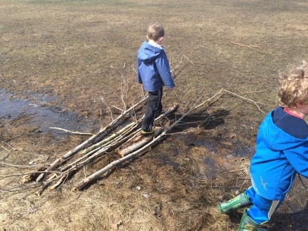 boy walking over bridge built with sticks