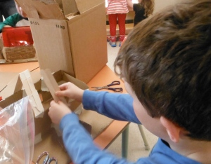 boy building roof trusses on cardboard model
