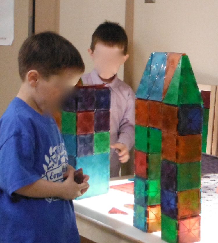 child building with magna tiles