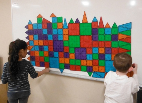 children building with mosaic tiles on a whiteboard