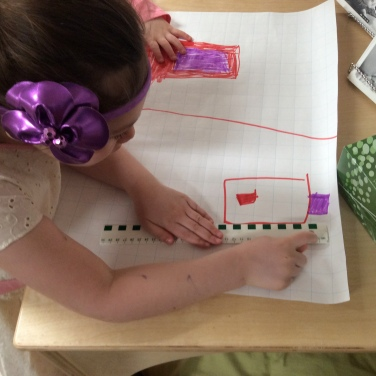 child measuring her drawing on grid paper