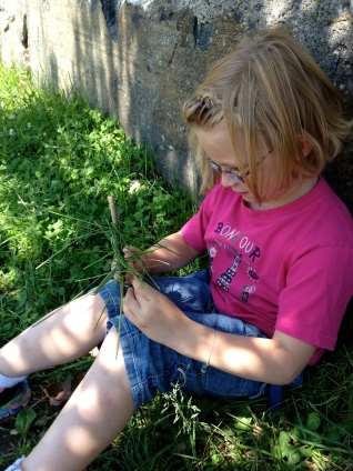 girl creating a tree using a stick and blades of glass