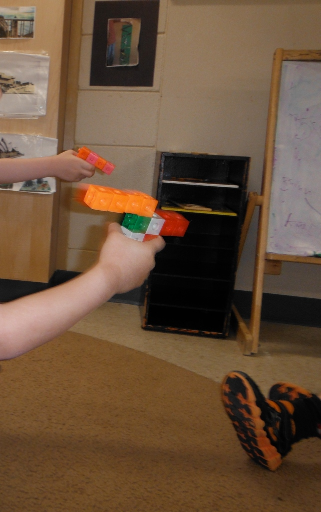 children's hands holding snap cube guns