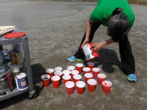 teacher pouring paint into solo cups