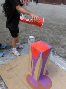 child pouring paint onto wooden tower